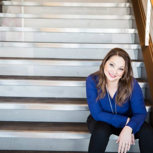 Amber De La Garza siting on steps